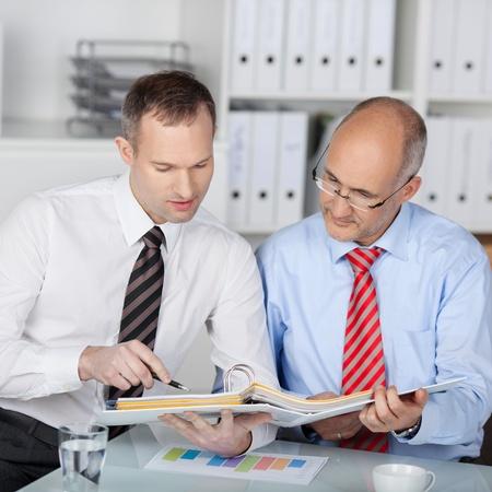 Dos colegas discutiendo un plan financiero con el consultor en la oficina
