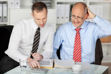 dismayed: Portrait of businessman consulting his mad partner at desk in office