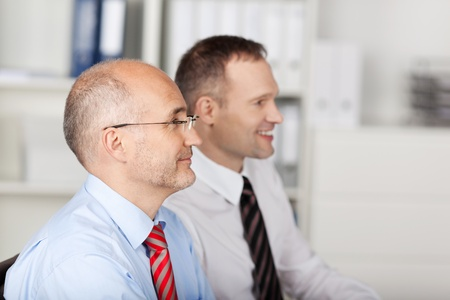 Image of two employees looking at businessperson explaining idea at the meeting photo