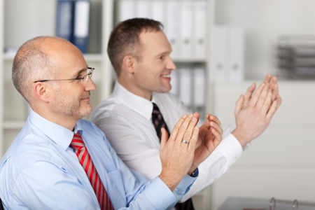 Business people clapping hands during meeting presentation at the office photo
