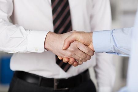 manos estrechadas: Cerca gesto de dos hombres de negocios dándose la mano Foto de archivo
