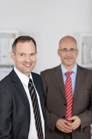 Two smiling businessmen standing at the office background photo