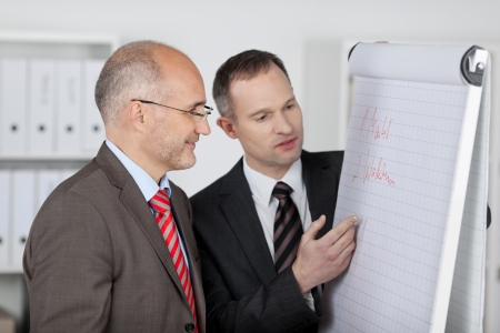 Businessman explaining with flipchart to his partner inside the office photo