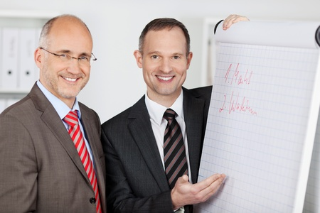 Close up businessmen standing and discussing at a flipchart photo