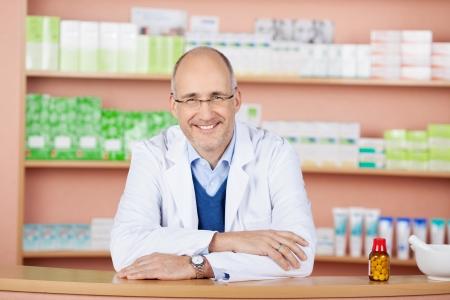 bata de laboratorio: Hombre de qu�mico farmac�utico de pie en la farmacia farmacia Foto de archivo
