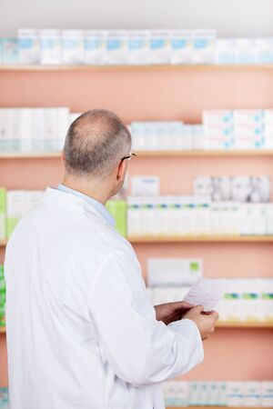 contemplated: Rear view of pharmacist chemist man working in pharmacy drugstore
