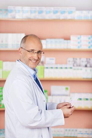 Smiling pharmacist chemist man working in pharmacy drugstore Stock Photo - 21146987