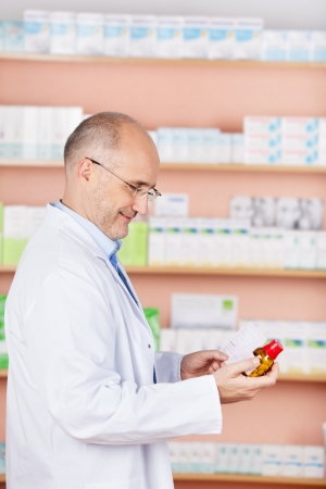 Portrait of a mature man pharmacist selecting a medication photo