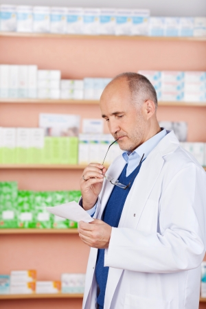 Mature male pharmacist standing in front of medicine looking prescription Stock Photo - 21146989