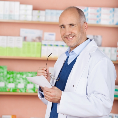 Smiling pharmacist standing in front of medicine check the prescription Stock Photo - 21146990