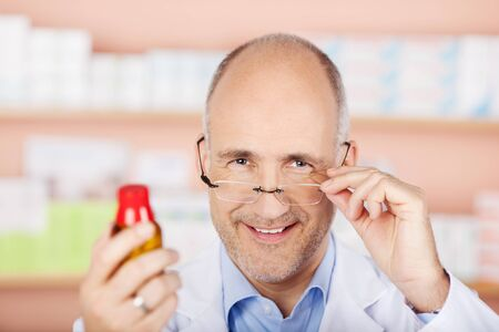 Male pharmacist holding glasses and shows the medicine in pharmacy photo