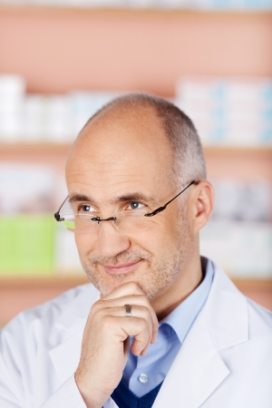 contemplated: Smiling pharmacist with glasses thinking over the store background