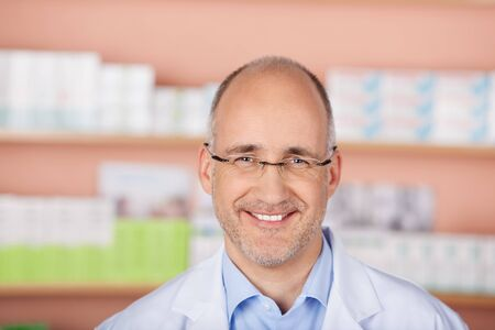 Smiling mature pharmacist standing in front of drugstore Stock Photo - 21146997