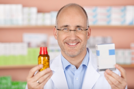 Happy pharmacist showing different medicines at the pharmacy photo