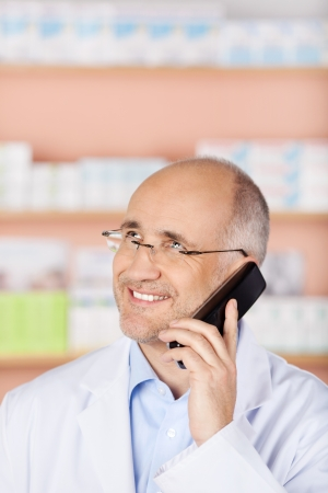 Smiling pharmacist calling through the telephone inside the store photo
