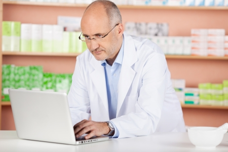 contemplated: Portrait of pharmacist browsing the internet using laptop in drugstore