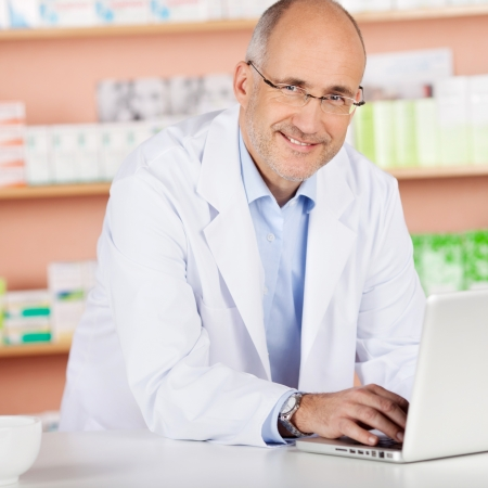 Cheerful pharmacist browsing the internet using laptop in drugstore photo