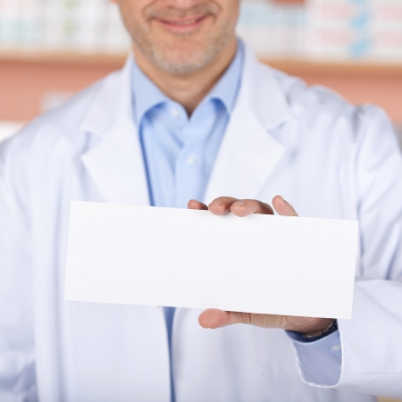 Smiling pharmacist showing the white envelope over the medicine background