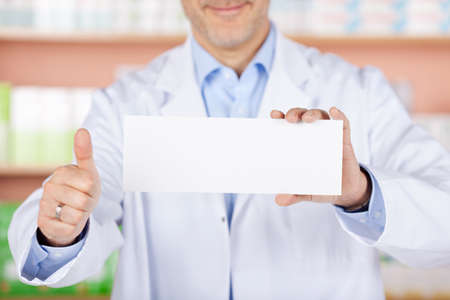 Close up pharmacist showing thumbs up and white envelope photo