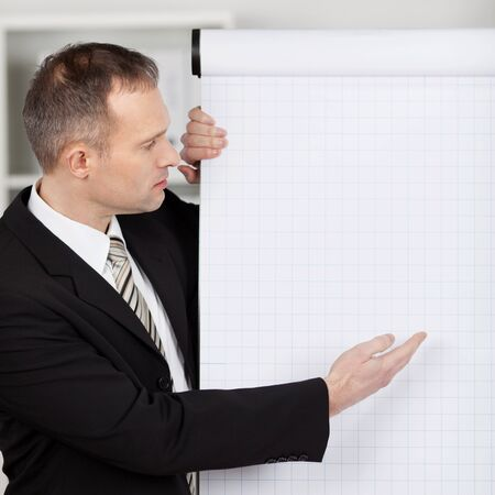 Manager in office pointing with index finger to empty flipchart photo