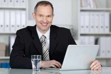 competent: Competent businessman working with laptop on the table Stock Photo