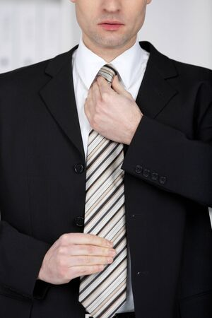 fastens: Handsome businessman fixing his tie in a close up shot