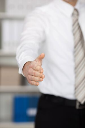 Conceptual gesture of business handshake over the blurred background photo