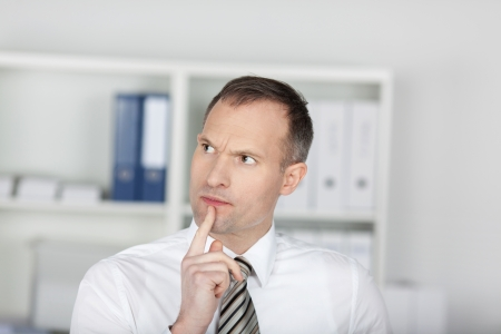 Close up shot of businessman thinking inside the office photo