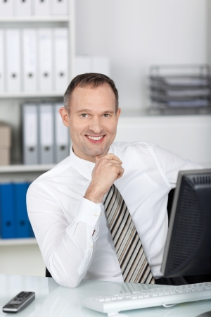 Happy businessman working in front of his computer table photo