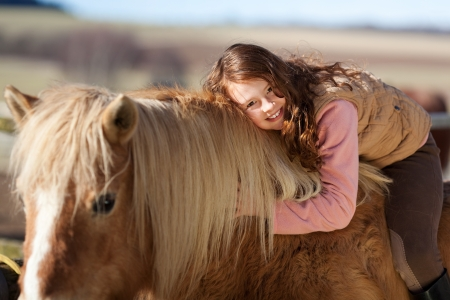 Smiling young girl out riding leaning forwards over the neck of her horse to pet and cuddle it in a show of affection photo