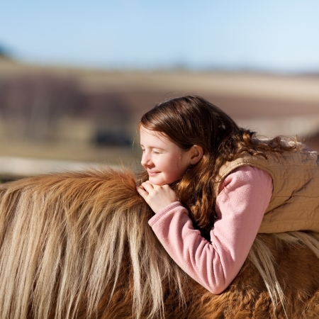 Young girl enjoying the sun laying on a palomino horse back photo