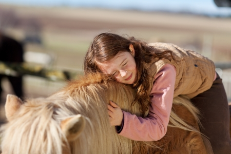 Pretty teenage girl loving her horse lying across its neck and mane with her eyes closed in contentment and bliss photo