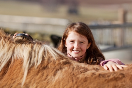 Pretty little girl brushing her horse and looking over the top of its back with a lovely smile