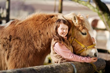 pony ride: Happy smiling girl poses next to her palomino horse near the paddock fence Stock Photo