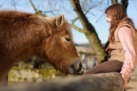 Smiling young girl and her palomino color horse in the outdoors photo