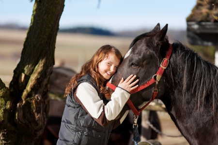 Portrait of a smiling young girl with a dark bay horse with red reins Stock Photo - 21147019
