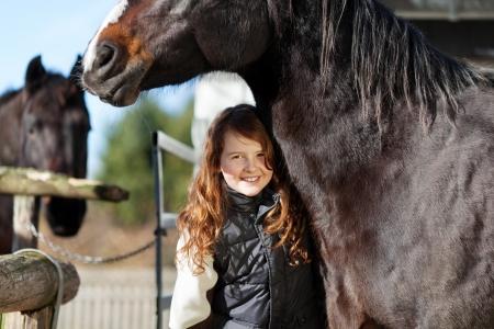 amigos abrazandose: Muchacha feliz joven que presenta bajo su oscura cabeza de caballo de la bahía Foto de archivo