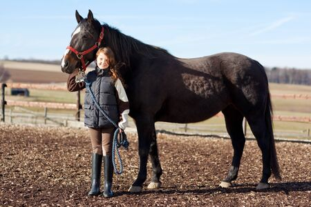 girl on horse: Portrait of a pretty young girl holding the reins of her dark bay horse Stock Photo