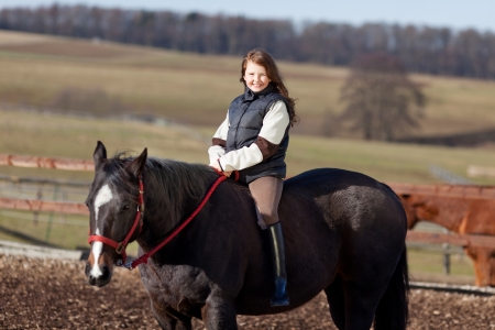 girl on horse: Portrait of a smiling young girl riding her dark bay horse on a bright sunny day Stock Photo