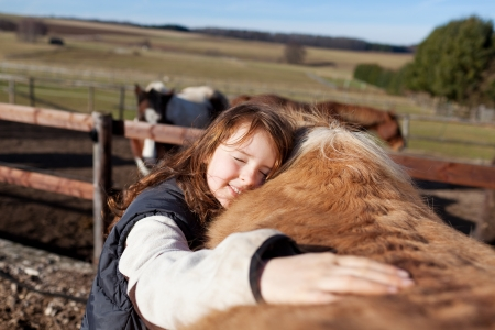 petting: Young girl petting her haflinger palomino horse in the back Stock Photo