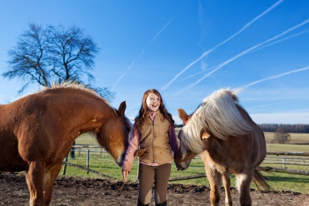 pony ride: Portrait of a pretty young girl with two palomino horses on the paddock on a sunny day