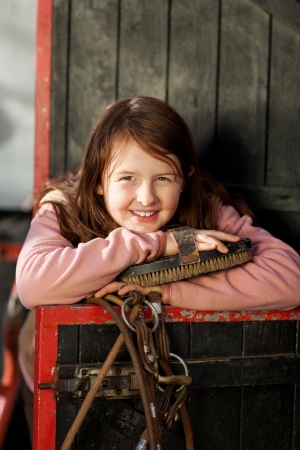 girl on horse: Portrait of a pretty young girl posing behind a stable door with the horse head piece and a large brush Stock Photo