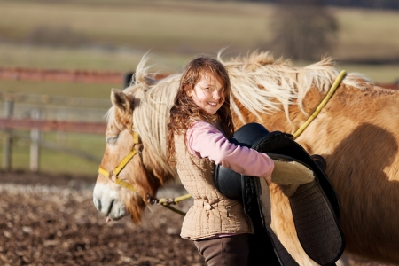 pony girl: Close-up of a young girl carrying saddle to put it on top of her palomino horse