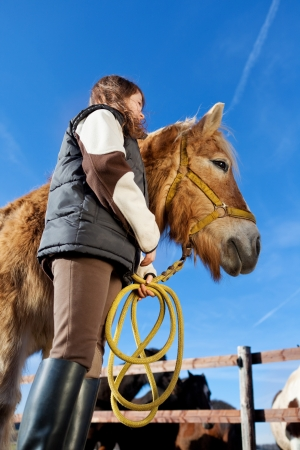 Low angle view of a girl holding the reins of her horse photo