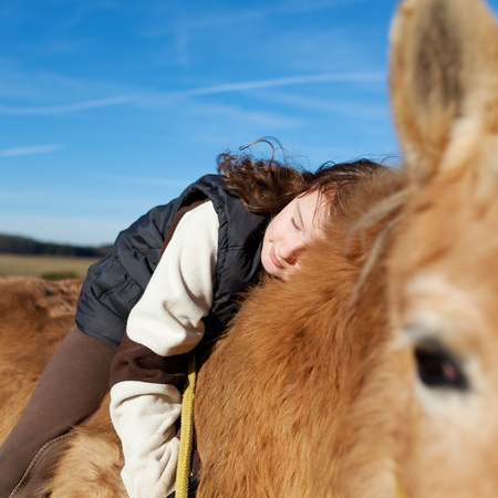 foe: Girl demonstrating affection foe her horse by laying on its back and holding its neck