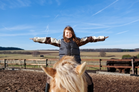 Happy girl playing as if she was flying on top of her horse photo