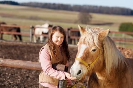 halter: Portrait of a happy smiling girl feeding her horse treats Stock Photo