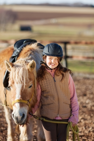 halter: Young girl leading horse to stable and wearing a modern horse riding helmet