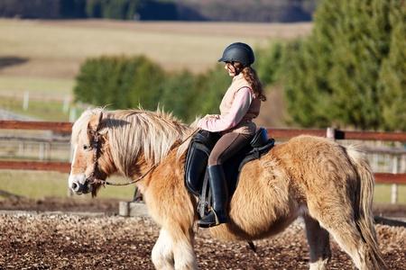 riding helmet: Perfil de una ni�a de montar a caballo que llevaba un casco de equitaci�n y botas Foto de archivo