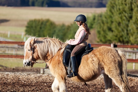 horse riding: Profile of a horse riding girl wearing a horse riding helmet and boots
